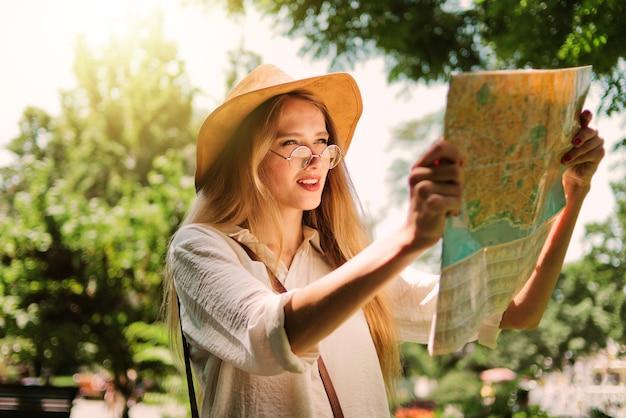Concetto di turismo, viaggi in nuove città. una giovane donna con un cappello di feltro gode di una mappa della città.