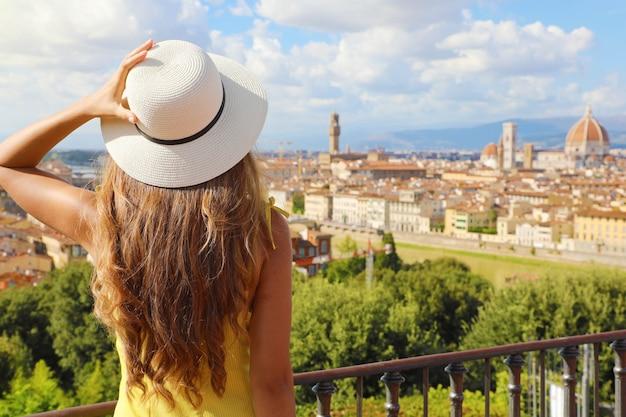 Turismo in italia. vista posteriore della giovane donna che tiene il suo cappello con la città di firenze sullo sfondo, toscana, italia.