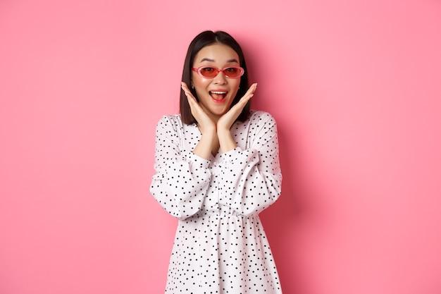 Il concetto di turismo e stile di vita ha entusiasmato la donna asiatica con occhiali da sole carini e vestito da urlo di felicità e...