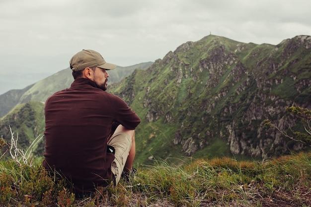 Turismo, montagne, stile di vita, natura, concetto di persone- giovane uomo in piedi in cima alla scogliera in montagne estive al tramonto e godersi la vista della natura