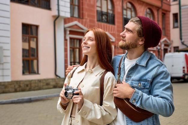 Turismo e tecnologia giovani coppie felici che prendono foto della città vecchia che viaggiano in europa a piedi in città ...