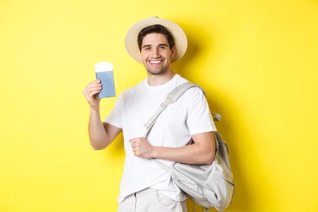 Turismo e vacanza. giovane ragazzo sorridente che va in viaggio, tiene in mano lo zaino e mostra il passaporto con i biglietti, in piedi su sfondo giallo.