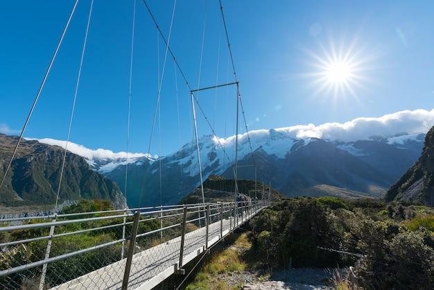 Turismo che cammina sul ponte sospeso attraverso il fiume in nuova zelanda