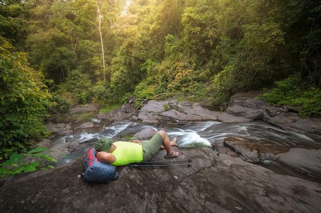 I turisti fanno trekking e si rilassano ascoltando il suono delle cascate vicino alla cascata nella foresta del parco nazionale di khao yai, thailandia. attività rilassanti presso la cascata per rilassarsi in vacanza.