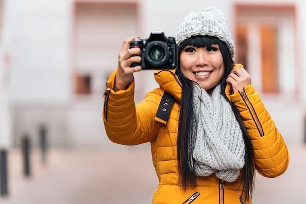 Donna asiatica turistica utilizzando la fotocamera in strada europea. concetto di turismo.