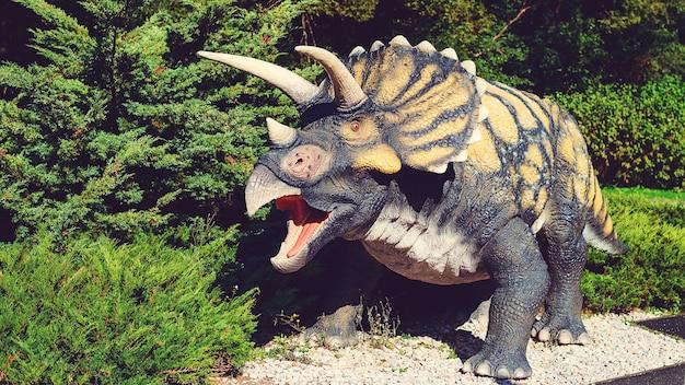 Attrazione turistica per bambini. dinosauro nel parco dei dinosauri. campo estivo, vacanza e giorno del fine settimana. posto preferito popolare con dinosauri per bambini. grande e moderno parco di dinosauri.