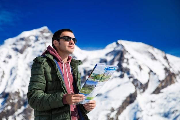 Turista sullo sfondo delle montagne innevate