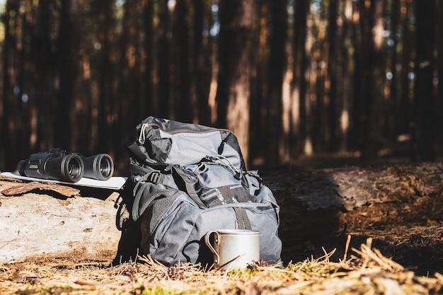 Zaino turistico, cappello, binocolo e una mappa su un tronco nella foresta