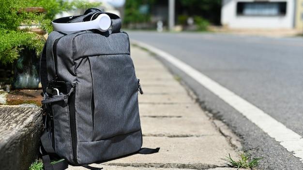 Zaino turistico e cuffie sulla strada in attesa dell'auto, concetto di viaggio.