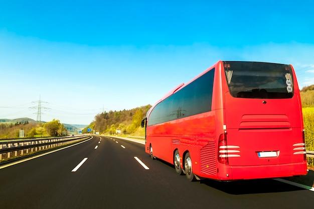 Bus turistico sulla strada dell'autostrada senza pedaggio dell'asfalto nel bello giorno di molla alla campagna
