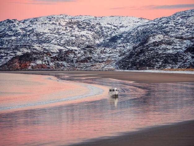Un autobus turistico viaggia nel traffico su una spiaggia bagnata tortuosa. incredibile paesaggio polare alba con catena montuosa innevata bianca all'orizzonte.