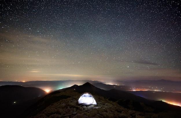 Accampamento turistico sulla cima della montagna sotto il cielo stellato notturno