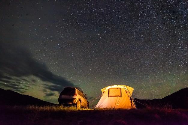 Campeggio turistico in mare di notte sotto il cielo nuvoloso. esiste un po' di rumore da alti iso