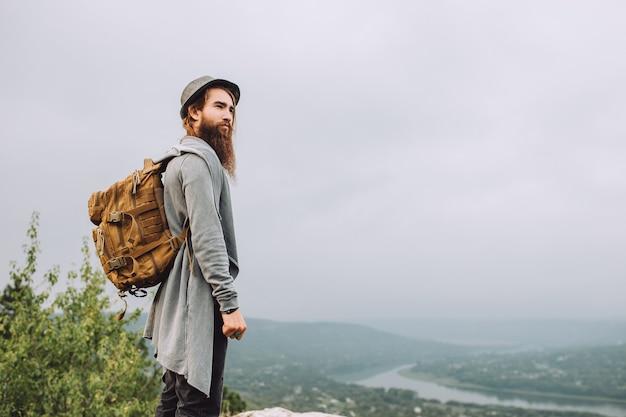 Turista che trasporta un grande zaino e cammina verso le montagne