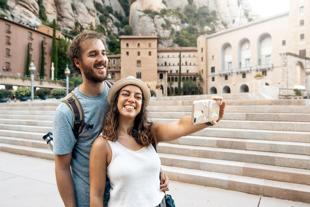 Coppia di turisti in vacanza prendendo una foto selfie nel monastero di montserrat, barcellona, spagna