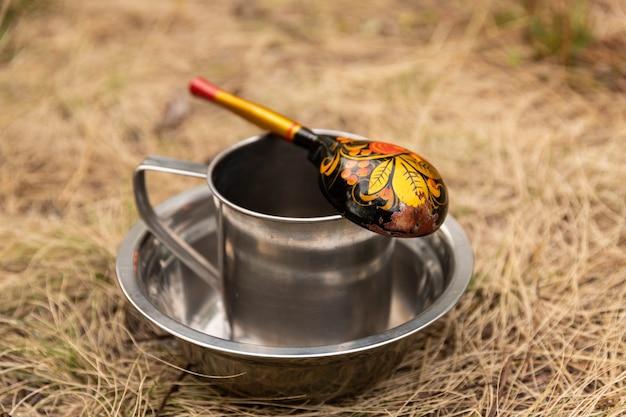 Una tazza turistica con un cucchiaio che si trova in un piatto sullo sfondo della natura.