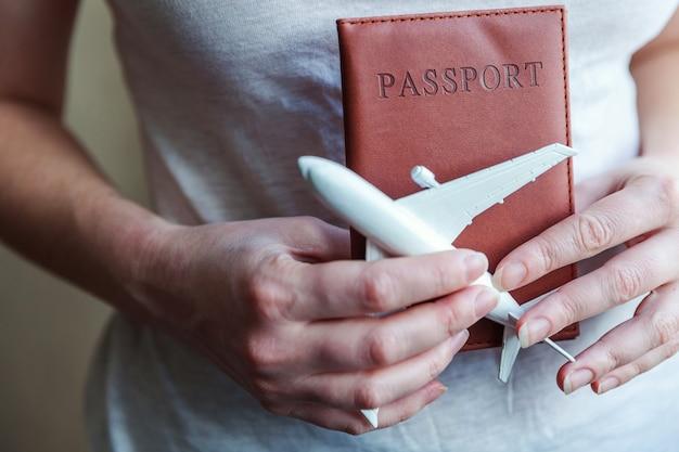 Elementi essenziali del turismo. mani femminili della donna che tengono piccolo aereo e passaporto del modello del giocattolo