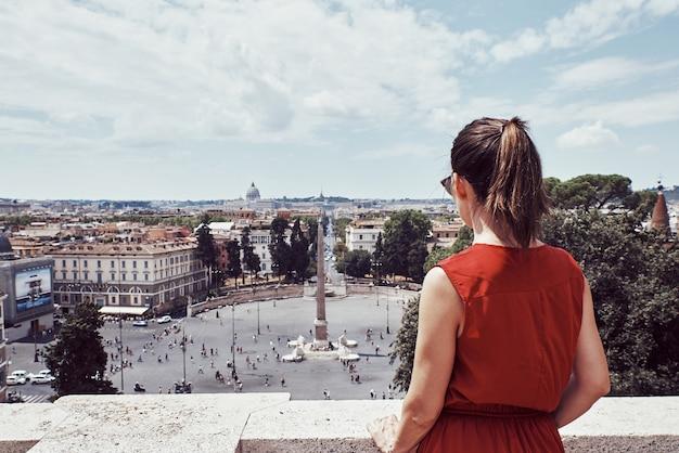 Ragazza turistica che osserva verso il popolo della plaza nella città di roma