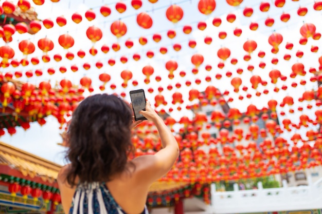 Una ragazza turistica fotografa le decorazioni festive di capodanno con lanterne cinesi del tempio cinese