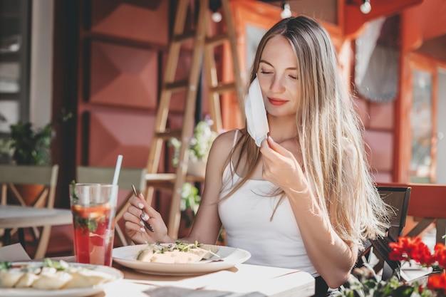 La ragazza turistica si siede da sola a un tavolo in un caffè, si toglie la maschera protettiva medica