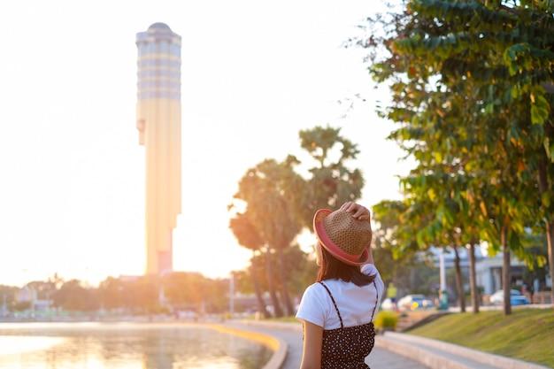 Ragazza turistica in piedi al parco guardando il famoso punto di riferimento della torre alla provincia di roi-et thailandia