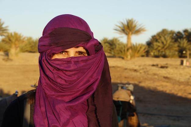 Una ragazza turistica con la sciarpa berbera nel deserto di merzouga
