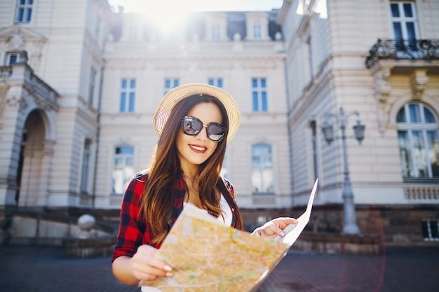 Ragazza turistica con capelli castani che indossa cappello, occhiali da sole e camicia rossa, tenendo la mappa sullo sfondo della città europea vecchia e sorridente, viaggiando.