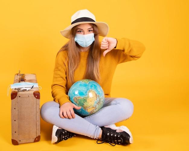 Una ragazza turistica con una mascherina medica, scoppio di coronavirus covid-19. concetto di viaggi cancellati. un turista non può partire a causa di una pandemia.