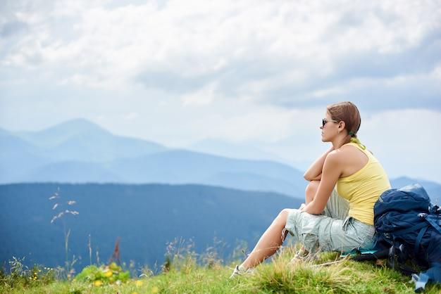 Turista sulla collina erbosa con zaino