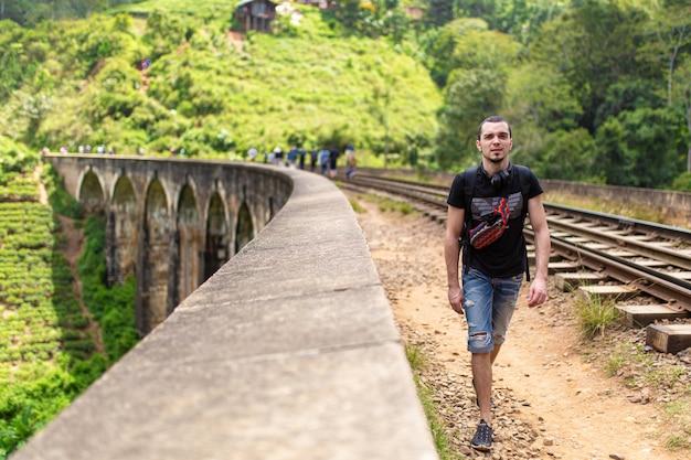 Un ragazzo turistico cammina lungo il famoso ponte ferroviario a nove arcate in sri lanka. turismo in luoghi pittoreschi