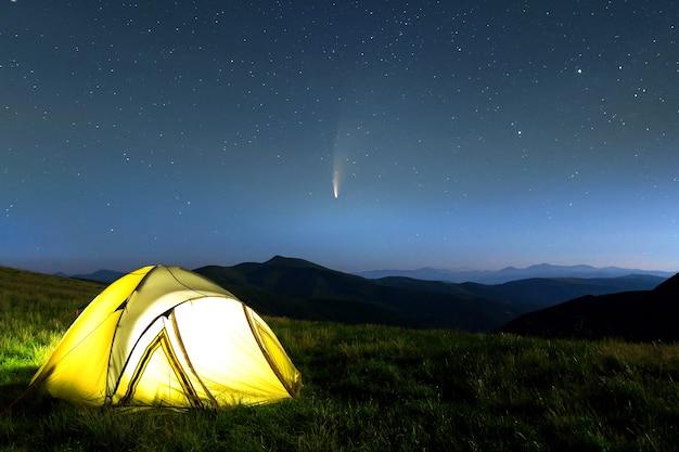 Tenda per escursionisti turistici in montagna di notte con stelle e cometa c/2020 f3 (neowise) con coda di luce nel cielo notturno scuro.
