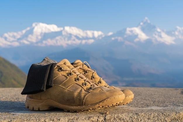 Scarpe da trekking turistiche con calze con cime innevate della catena dell'annapurna sullo sfondo. trekking in montagna e concetto di escursionismo, viaggi e turismo. primo piano foto d'archivio.