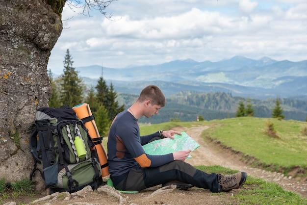 Il turista sta studiando una mappa della zona seduta sotto un albero lungo la strada