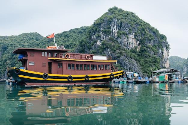 Giunche turistiche (barche) e villaggio galleggiante nella baia di ha long, vietnam. pittoresco paesaggio marino con riflesso