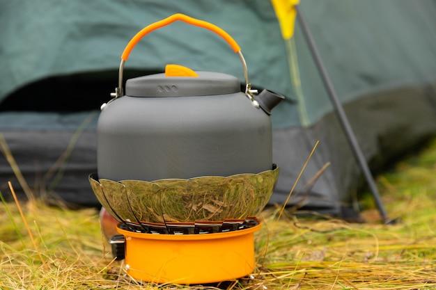 Bollitore turistico su un bruciatore a gas. cucinare in condizioni di campo. utilizzando un bruciatore a gas turistico