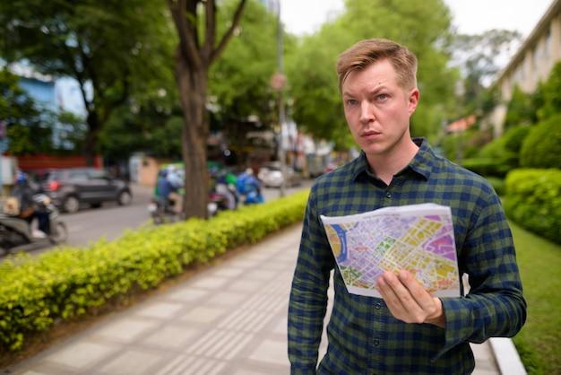 Uomo turistico che esplora la città di ho chi minh nel vietnam e che tiene mappa