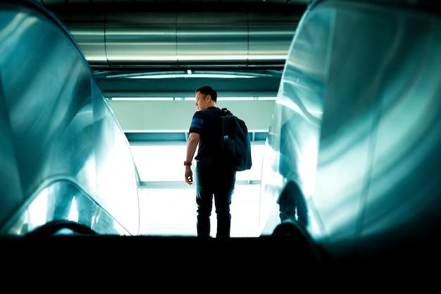 Uomo turistico salendo sulle scale della scala mobile.
