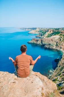 Uomo turistico all'aperto sul bordo della scogliera in riva al mare