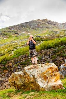 Uomo turistico fotografa una bella vista da un'altezza sul suo smartphone. anziano uomo barbuto fa una foto del paesaggio.