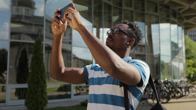 Uomo turistico che scatta foto con il telefono con fotocamera al di fuori del giovane uomo afroamericano che scatta foto al telefono per strada