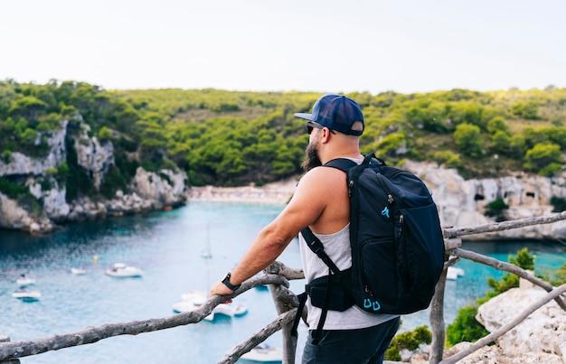 Un turista con uno zaino gode della vista di una baia della spiaggia di macarella