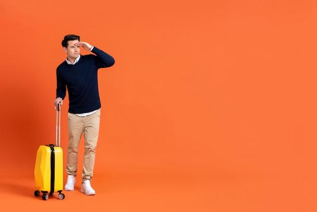 Uomo turistico con bagaglio pronto per il viaggio che osserva via