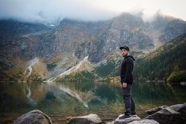 Turista vicino al lago di montagna morskie oko nel parco nazionale dei tatra, polonia. uomo felice dell'escursionista sul pittoresco lago di montagna in autunno.