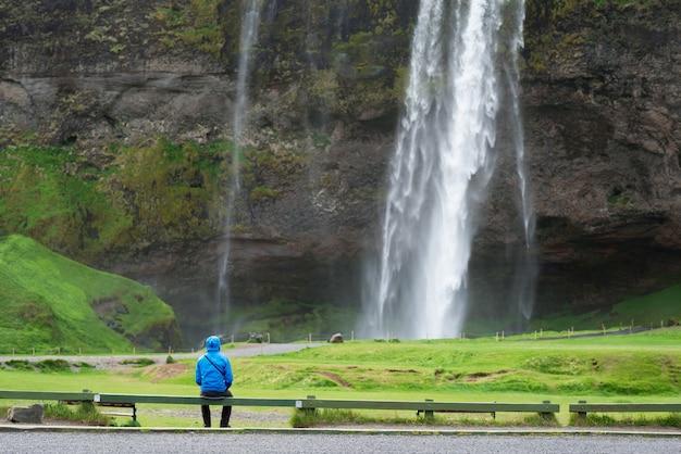 Turista vicino ad una cascata di seljalandsfoss in islanda