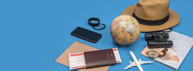 Vacanze di pianificazione turistica con l'aiuto della mappa del mondo con altri accessori da viaggio in giro. smartphone, fotocamera a pellicola e occhiali da sole su sfondo blu.