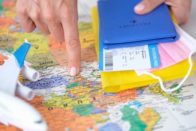 Il turista punta il dito sul biglietto aereo per la grecia sulla mappa del mondo e tiene il passaporto in viaggio e