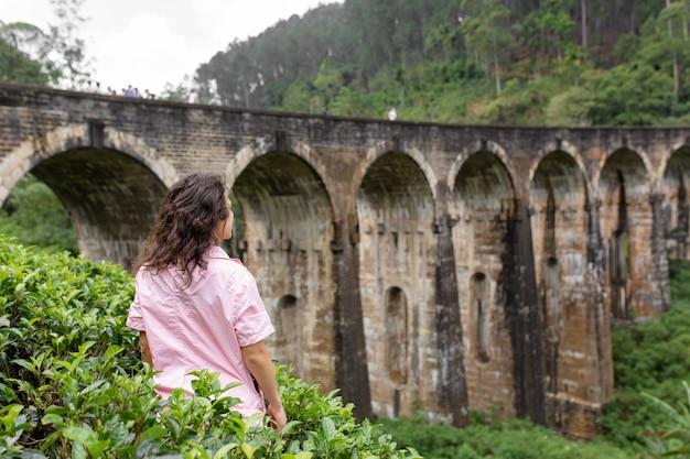 Un turista pone in una piantagione di tè vicino al famoso ponte a nove arcate in sri lanka. turismo in luoghi pittoreschi