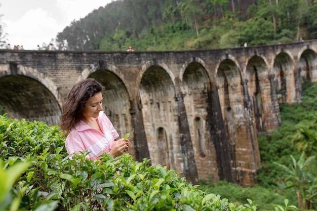 Un turista pone in una piantagione di tè vicino al famoso ponte a nove archi in sri lanka. turismo in luoghi pittoreschi