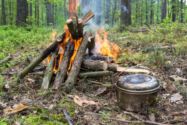Pentola turistica vicino al fuoco. cuocere a fuoco aperto. utensili da cucina da campeggio. attività di trekking estivo