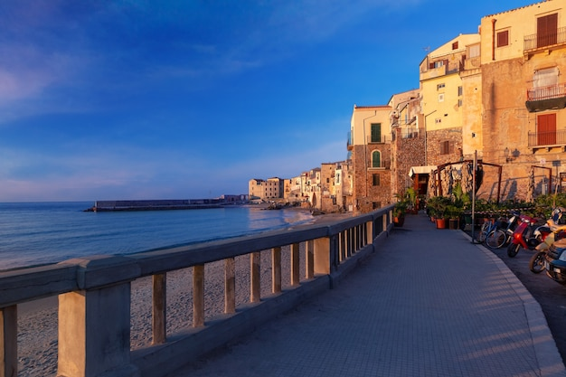 Passeggiata turistica e spiaggia vuota nel centro storico della città costiera di cefalù al tramonto, sicilia, italia
